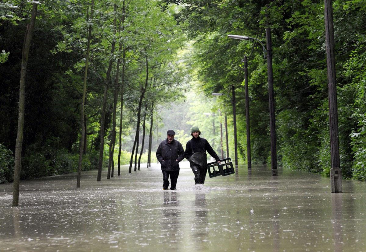 Люди идут по затопленной улице под дождем