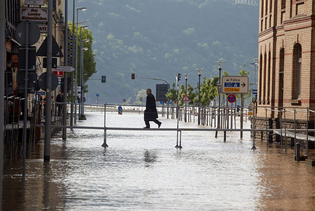 Мужчина переходит через затопленную улицу