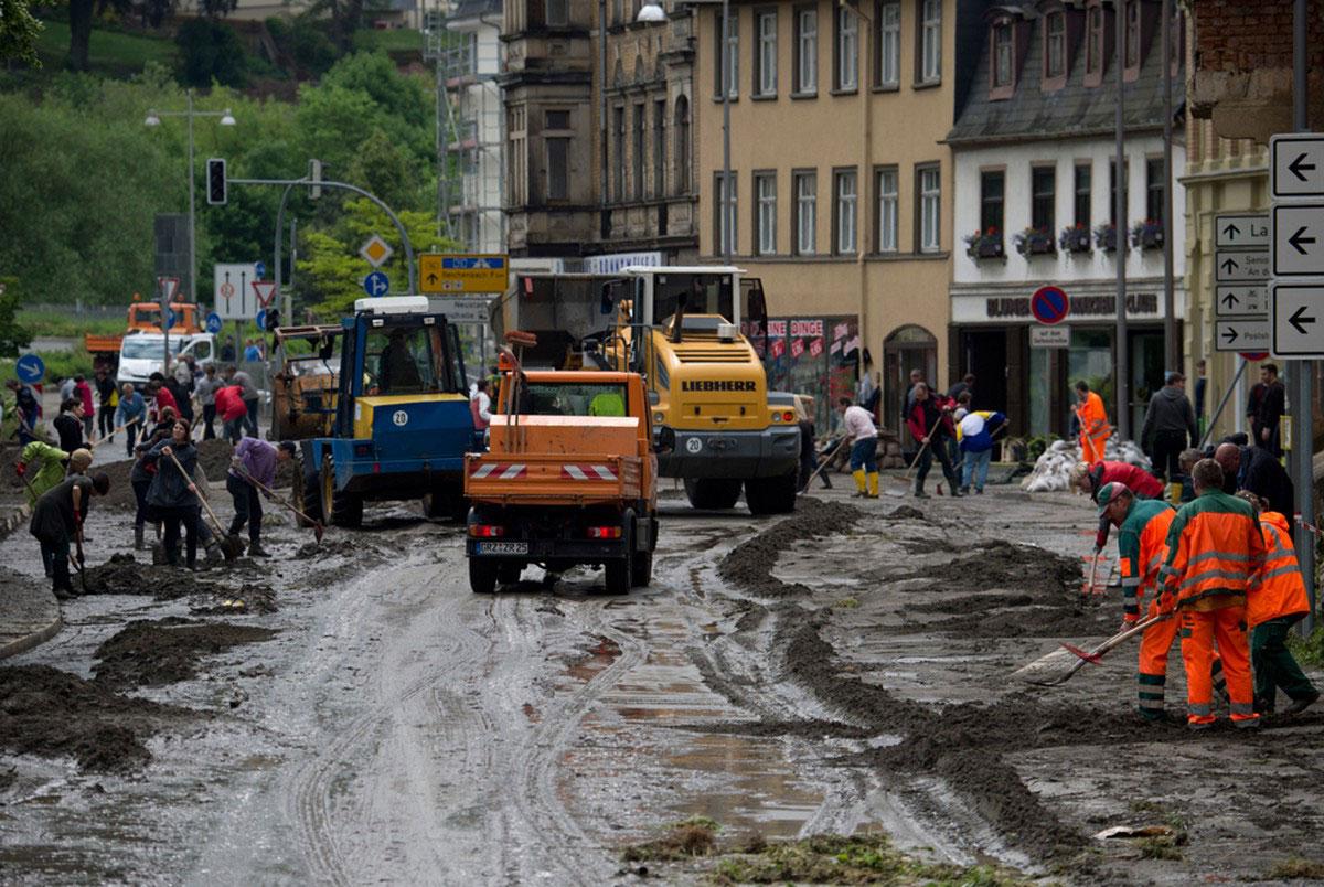 люди за уборкой улиц после наводнения