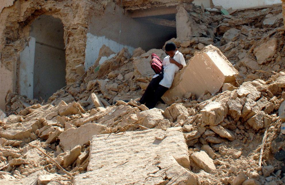 мальчик на развалинах своего дома, фото