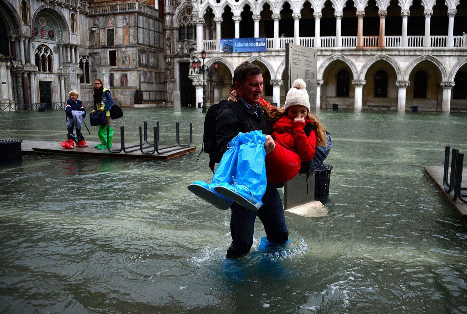мужчина с девочкой на затопленной площади Италии, фото