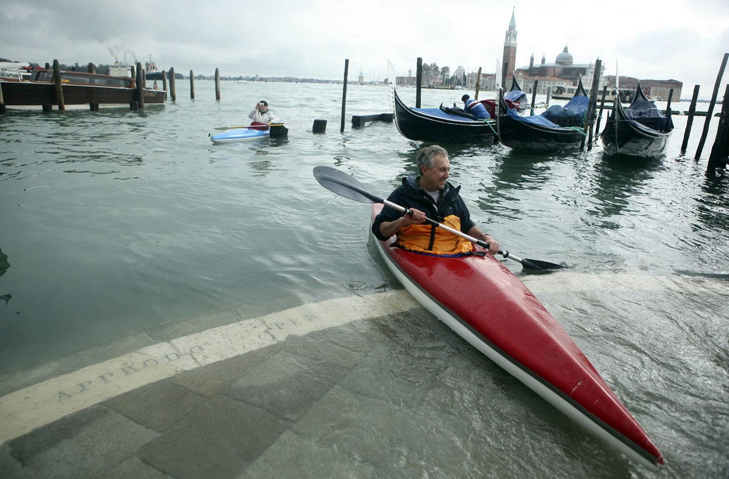 мужчина на байдарке в затопленной Венеции