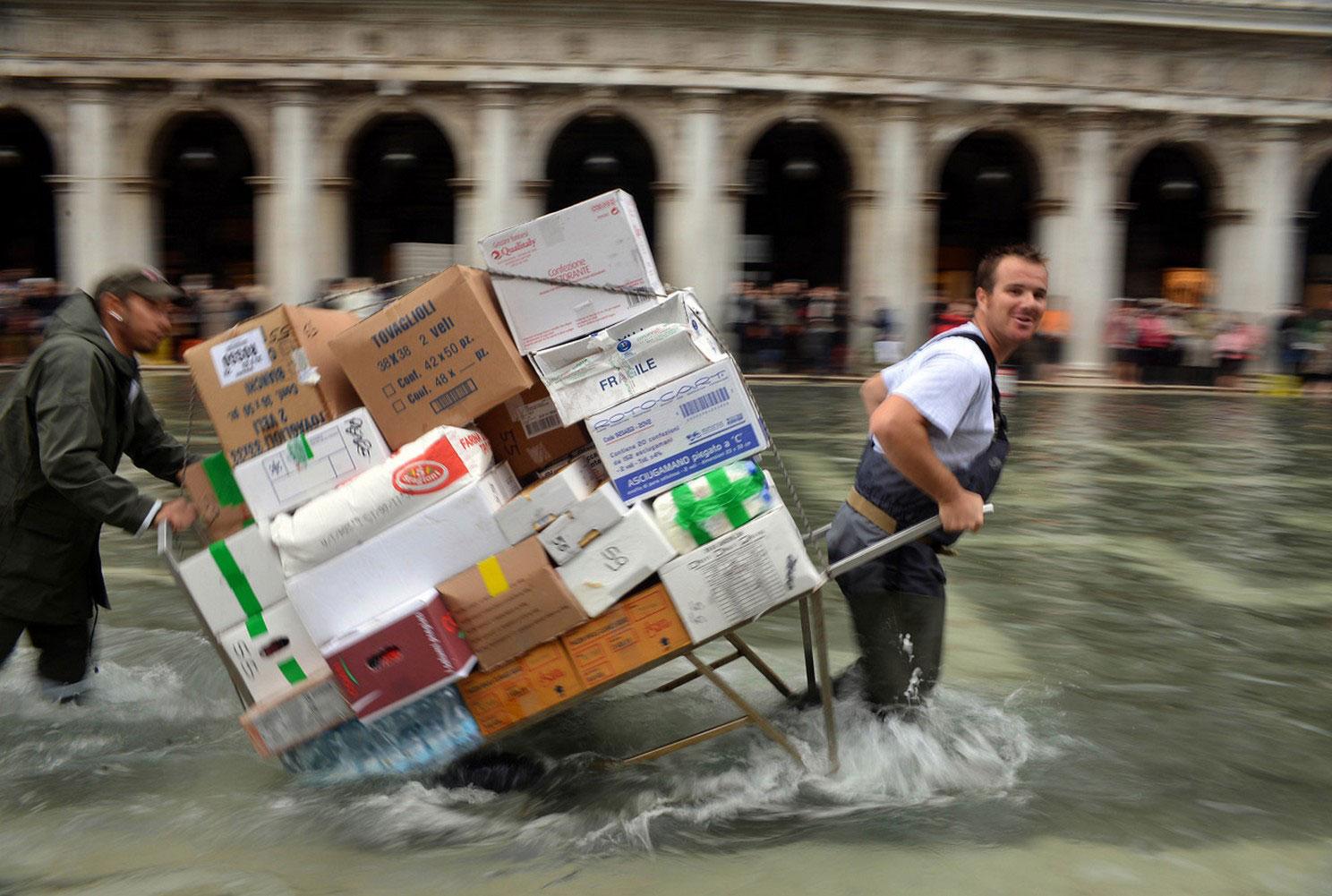 работники везут коробки по затопленной площади, фото