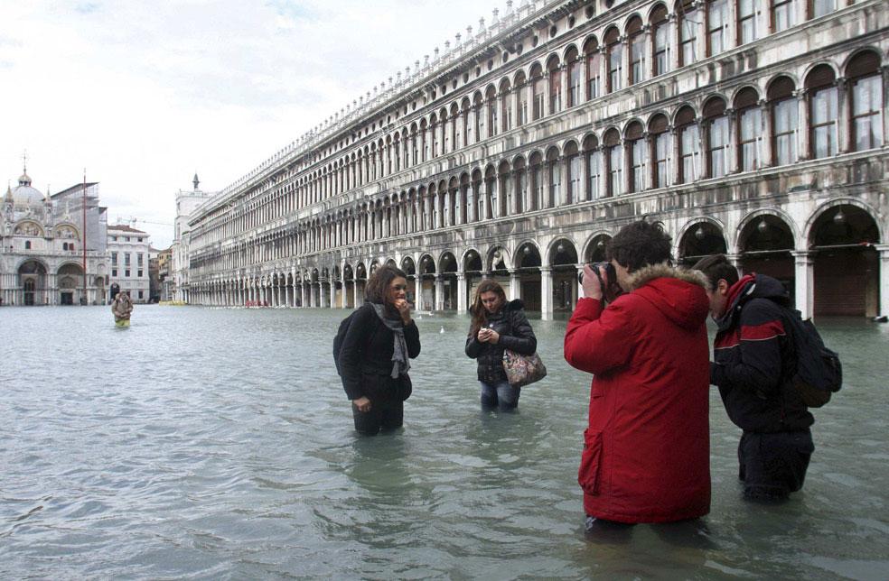 туристы фотографируются на затопленной площади, фото