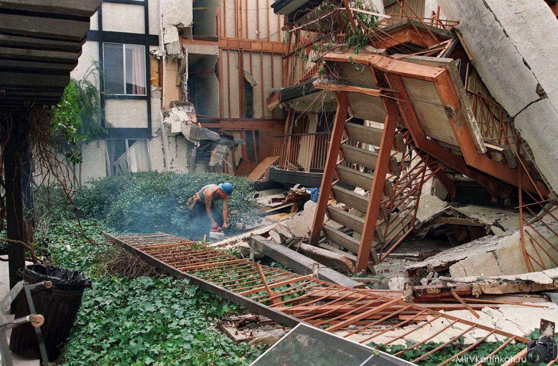 строитель на обломках дома