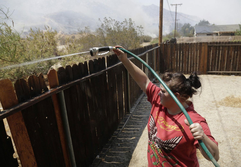 женщина поливает из шланга