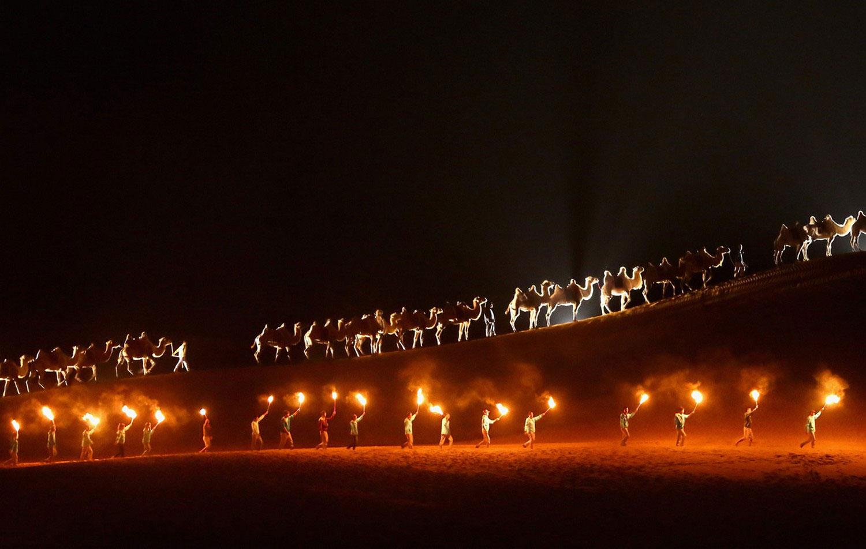 караван верблюдов при факелах