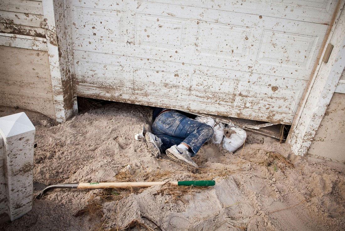мужчина лезет под дверь своего гаража, фото