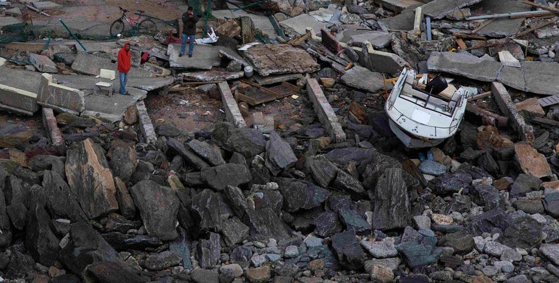 Мужчины стоят возле лодки, которую ураган выкинул на берег, фото