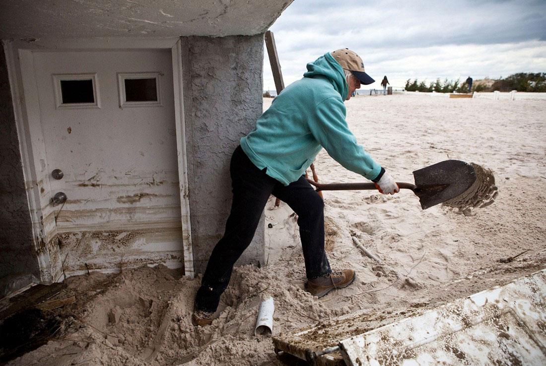 Женщина расчищает от песка вход в свой разрушенный дом, фото