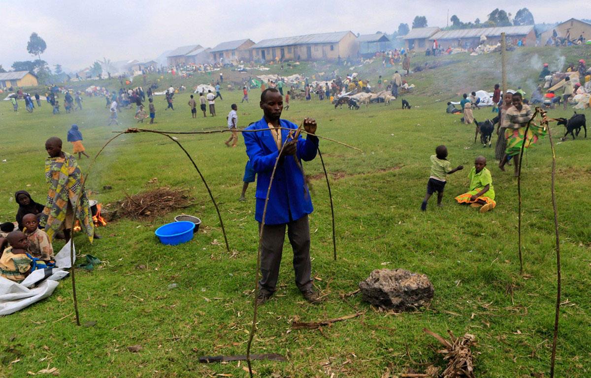 беженец сооружает в поле жилье