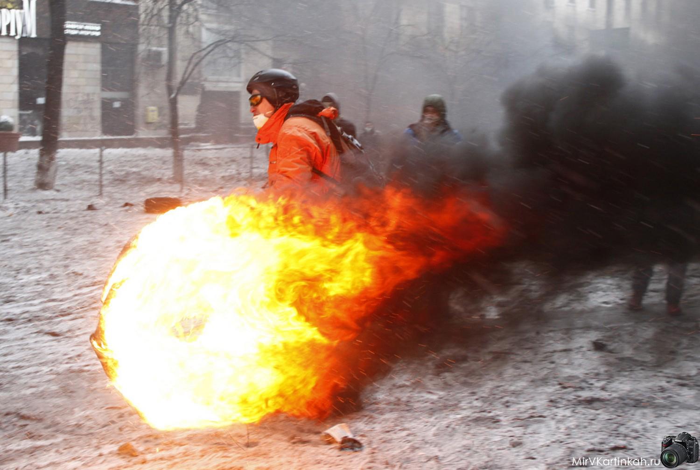 Мужчина катит горящую автомобильную покрышку