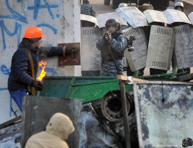 Участник митинга готовится бросить бутылку