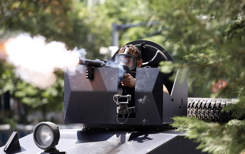Офицер ОМОНа стреляет по толпе демонстрантов слезоточивым газом