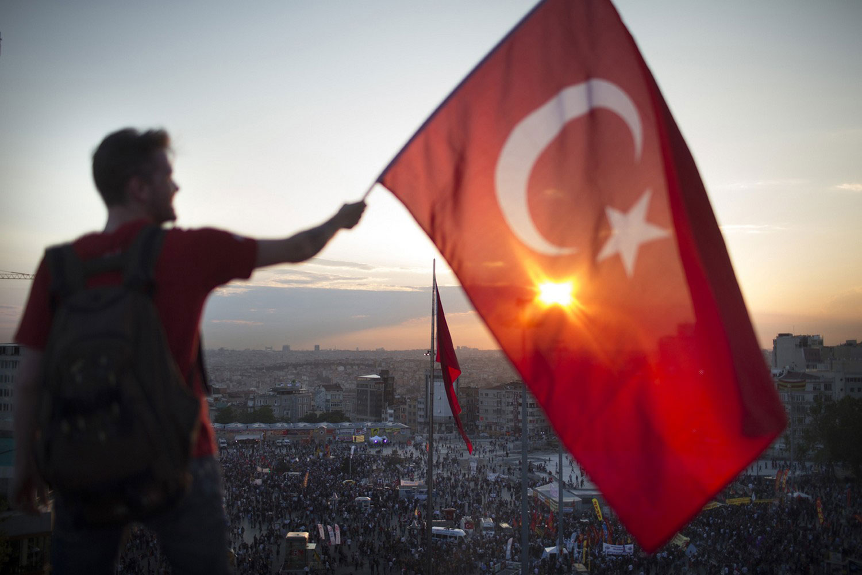 Протестующий размахивает турецким флагом
