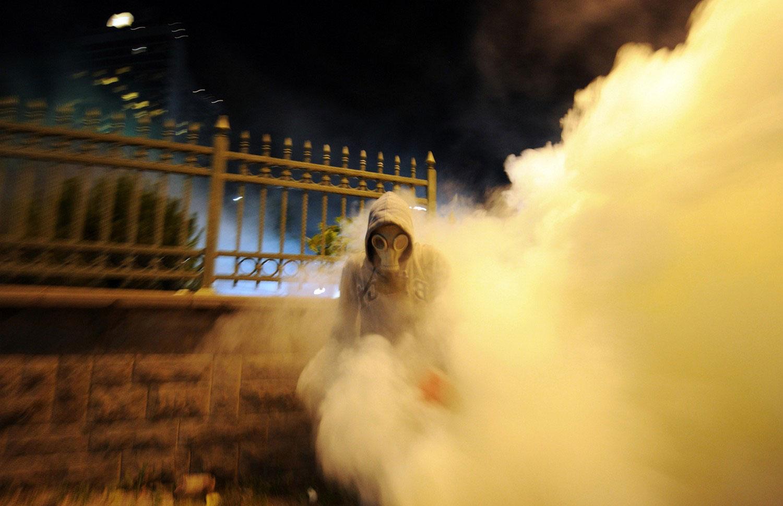 Мужчина убегает от слезоточивого газа
