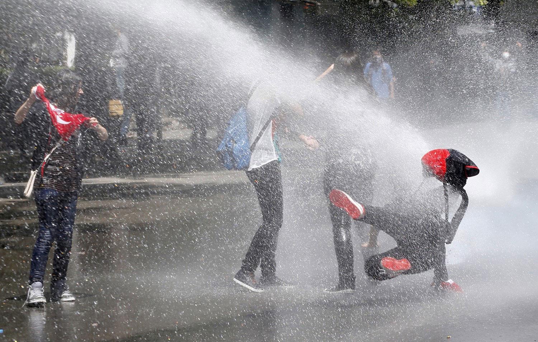 Люди под мощным напором струи из водомета