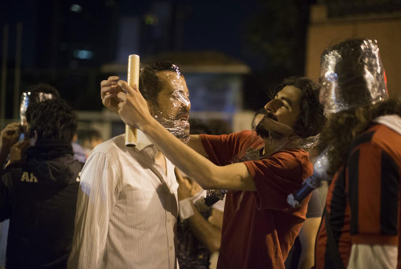 протестующие заматывают лица пленкой