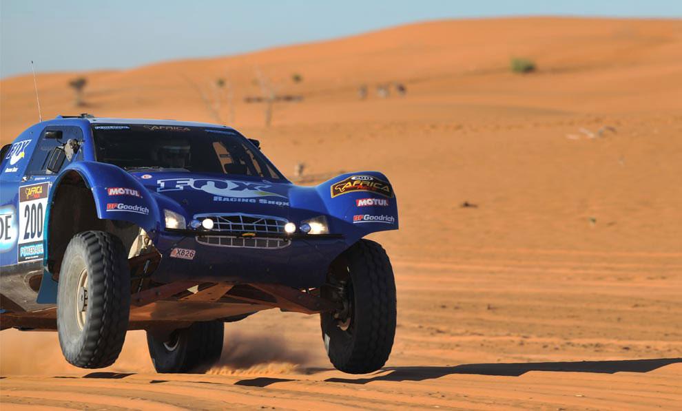 автогонщик на спортивном автомобиле, фото с ралли Дакар