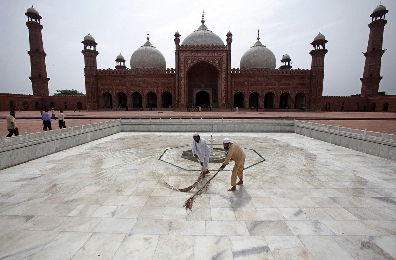 мужчины чистят фонтан перед мечетью