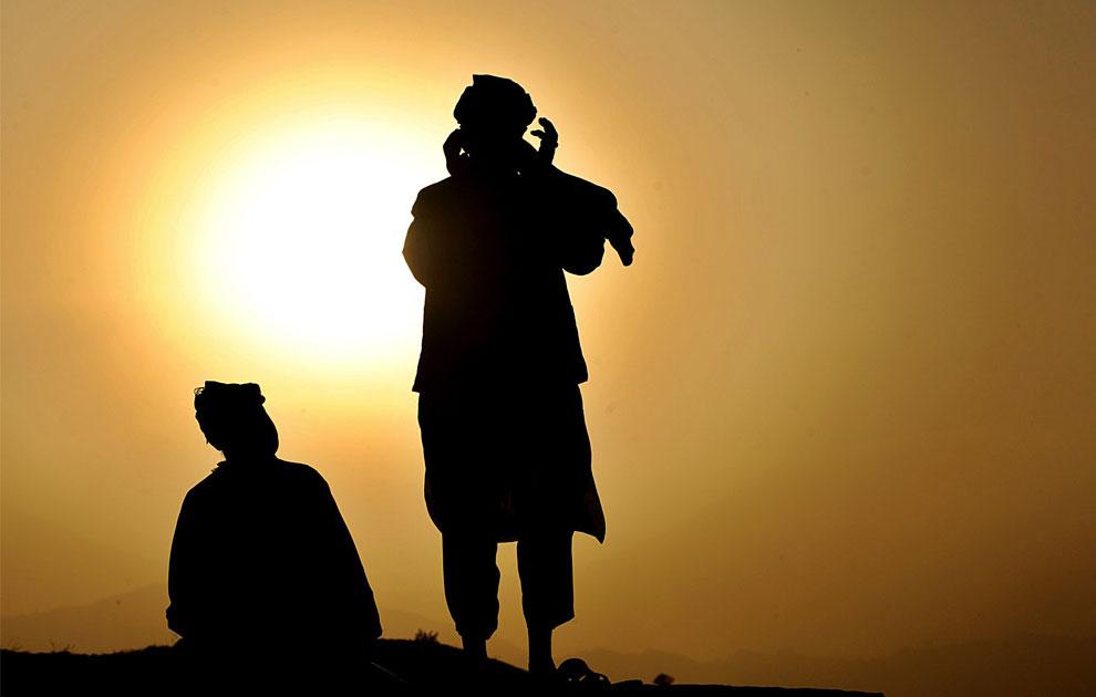 Афганские мужчины молятся на вершине холма во время Рамадана, фото