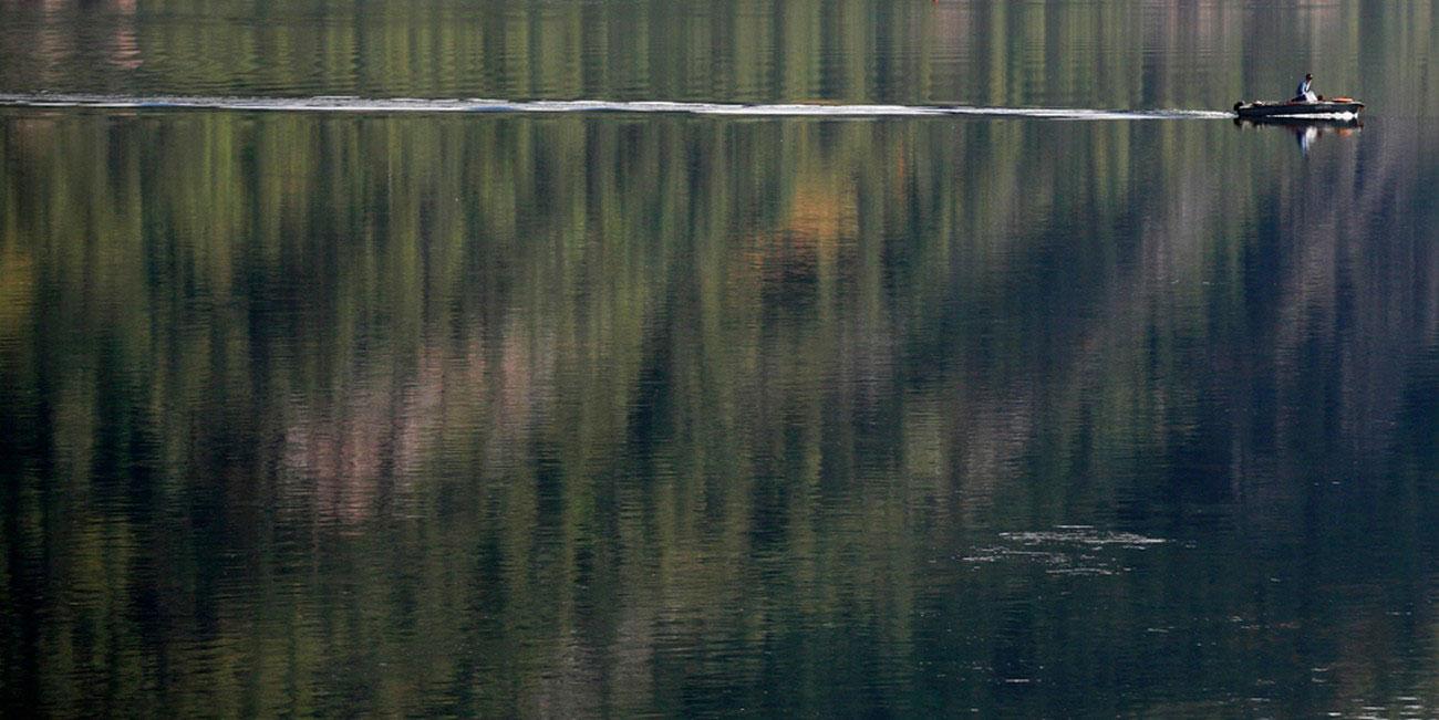 моторная лодка мчится по сибирской реке