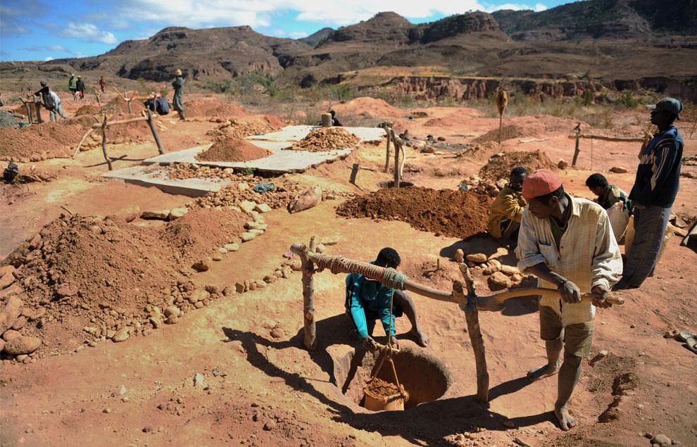 шахтеры вытаскивают мешок гравия из глубокой ямы, фото