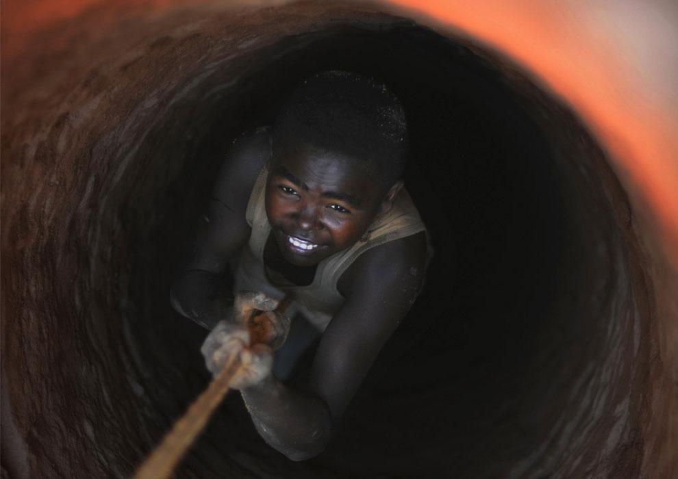 шахтер опускается в яму в земле, фото