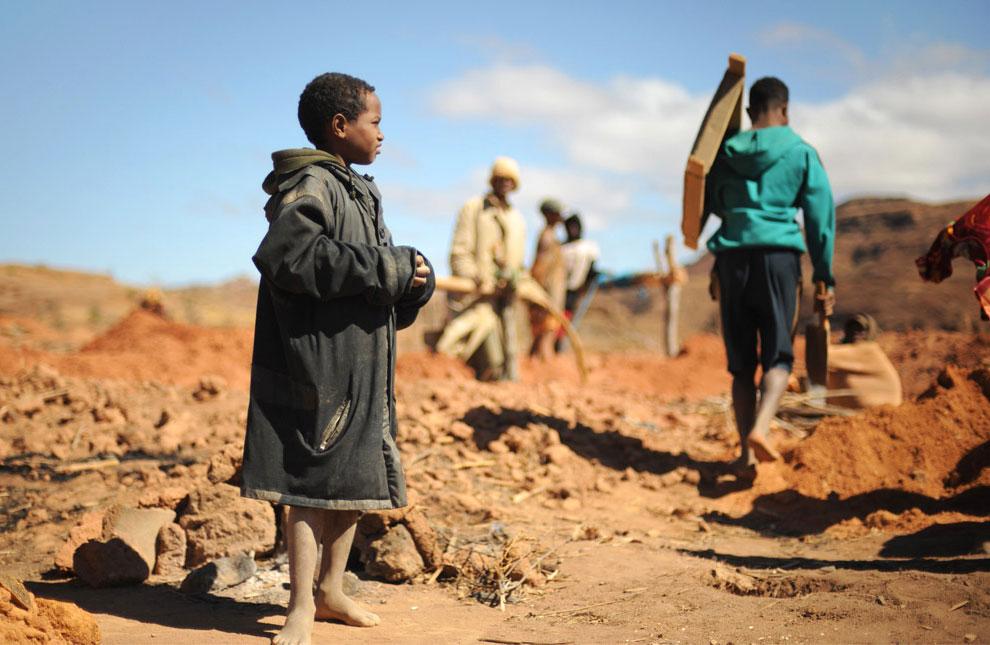 мальчик наблюдает, как шахтеры извлекают из ямы гравий с сапфирами, фото