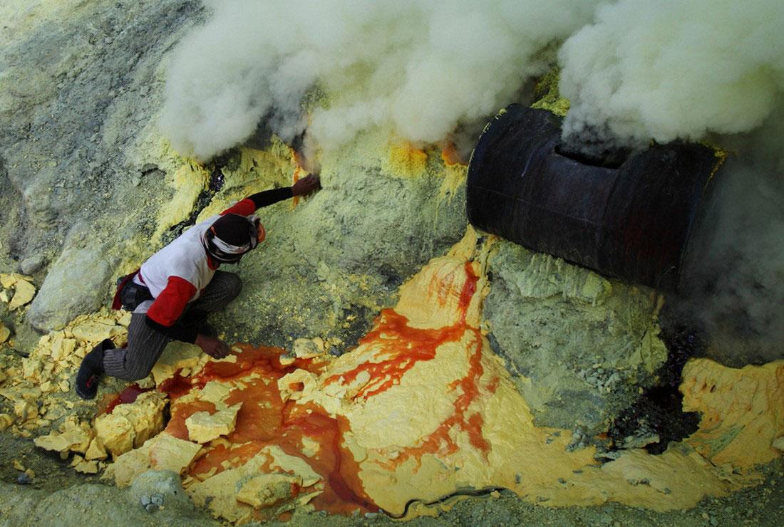 Шахтер извлекает серу из трубы, фото