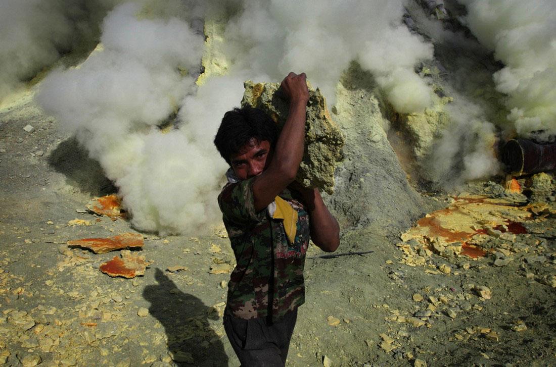 Шахтер несет серу из вулкана к своим корзинам, фото