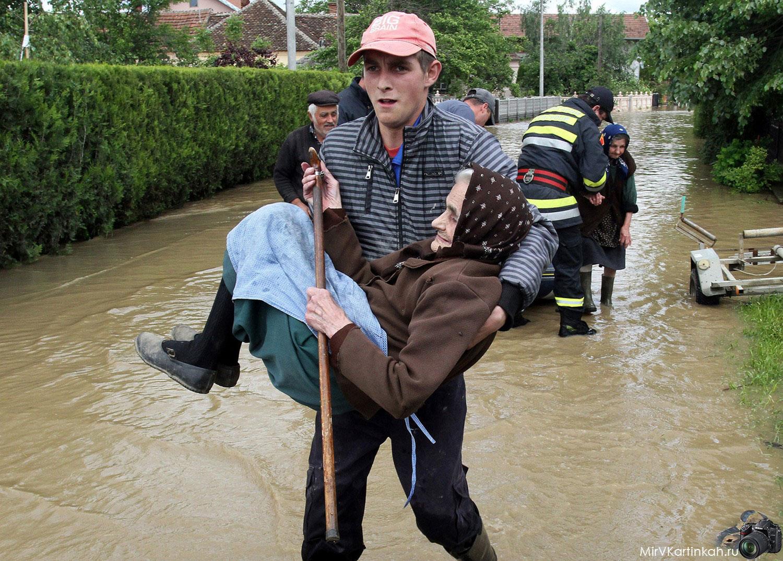 спасатель несет пожилую женщину