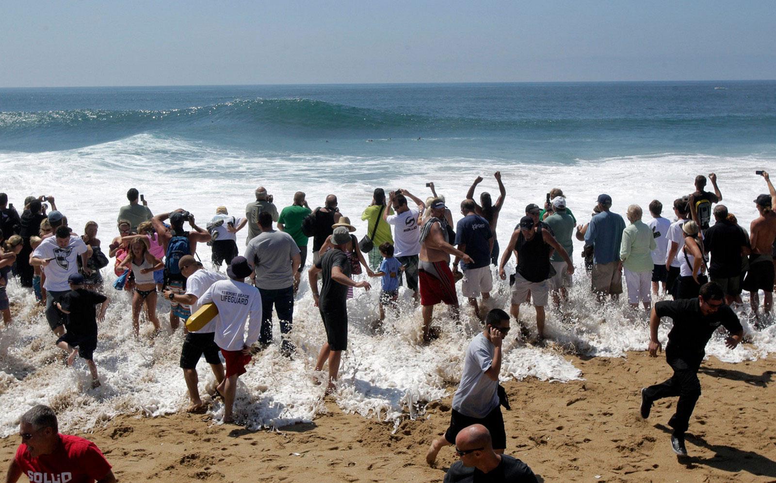 волна окатила людей на пляже