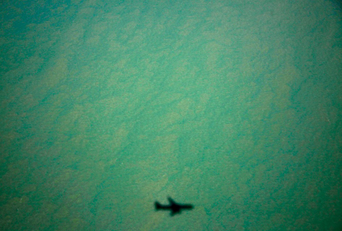 тень самолета над бухтой