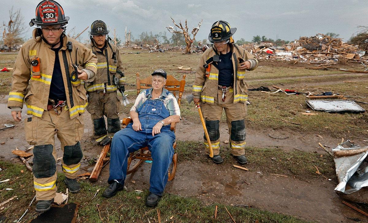 Пожарные возле старика в кресле-качалке