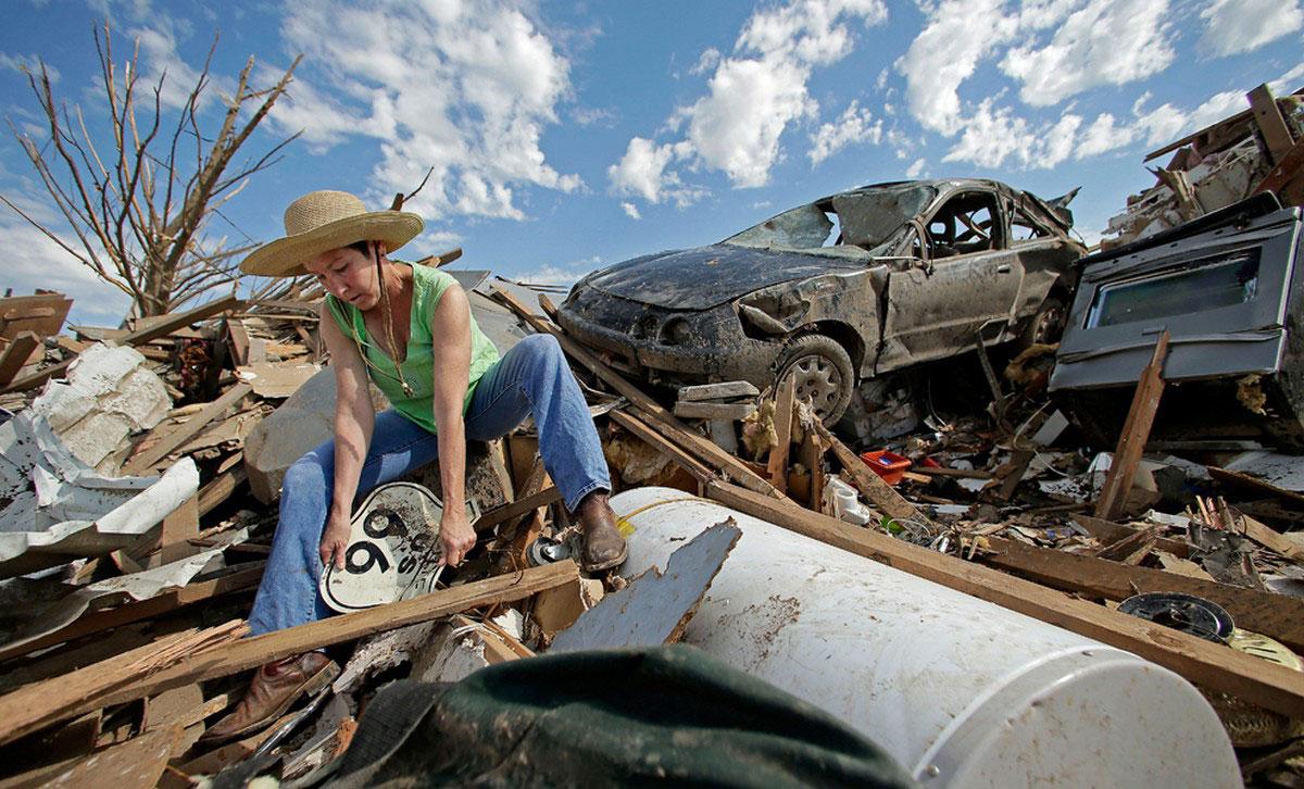 местная жительница на месте разрушенного смерчем дома