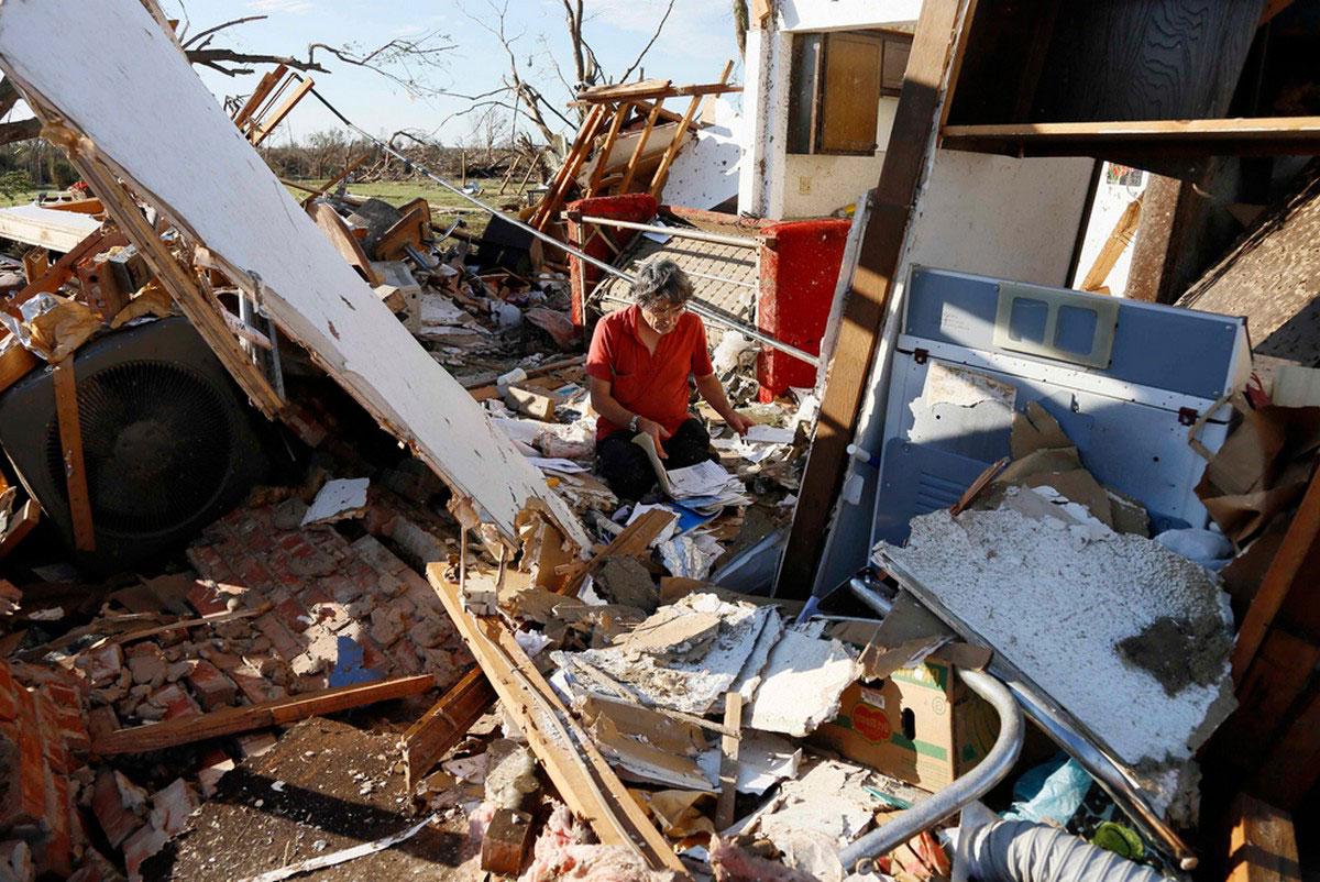 местный житель собирает документы после налетевшего урагана