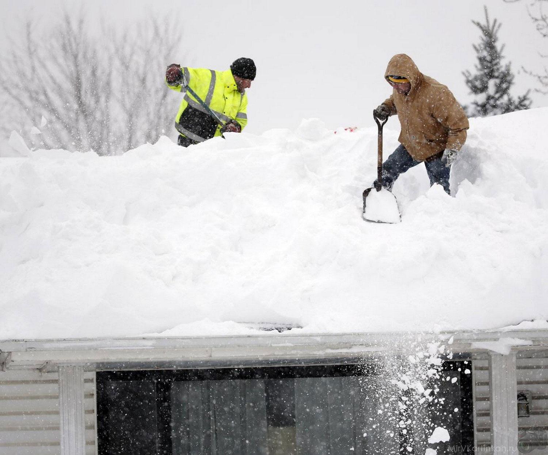 Мужчины расчищают от снега крышу дома