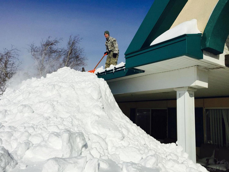 люди сбрасывают снег с крыш