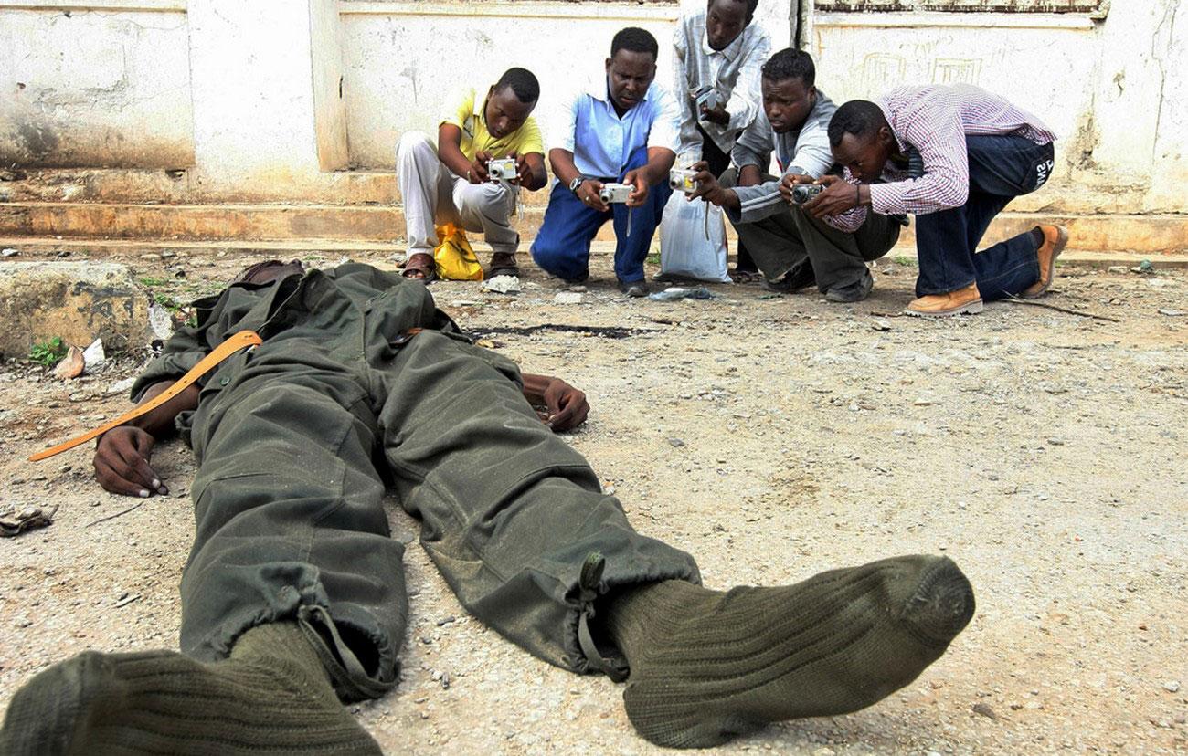 Местные журналисты фотографируют труп