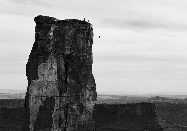 мужчина прыгает со скалы