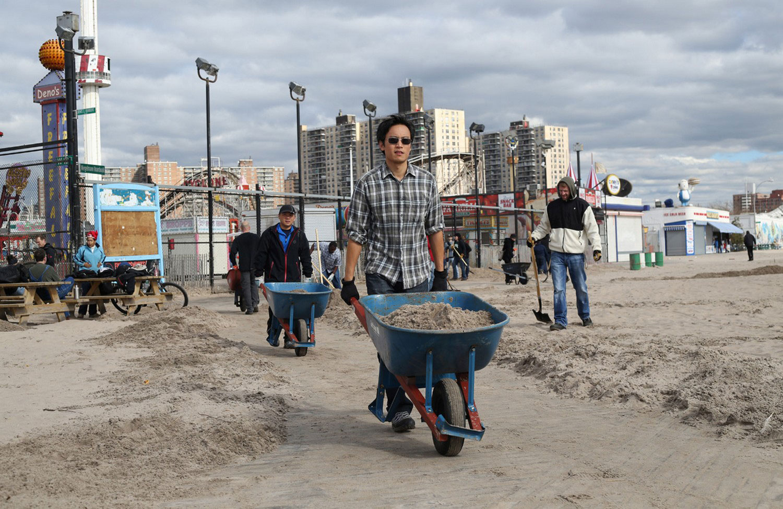 Люди вывозят песок принесенный штормом, фото урагана Сенди