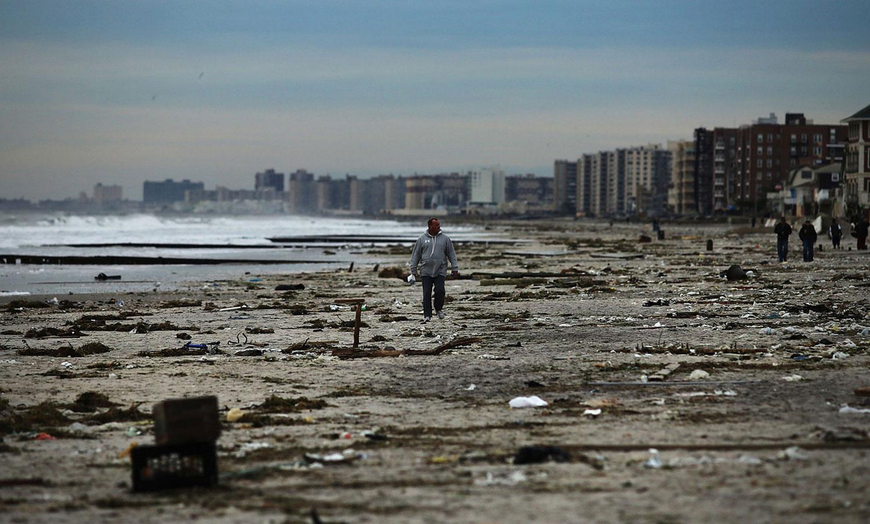 Мужчина идет по загрязненному пляжу после шторма