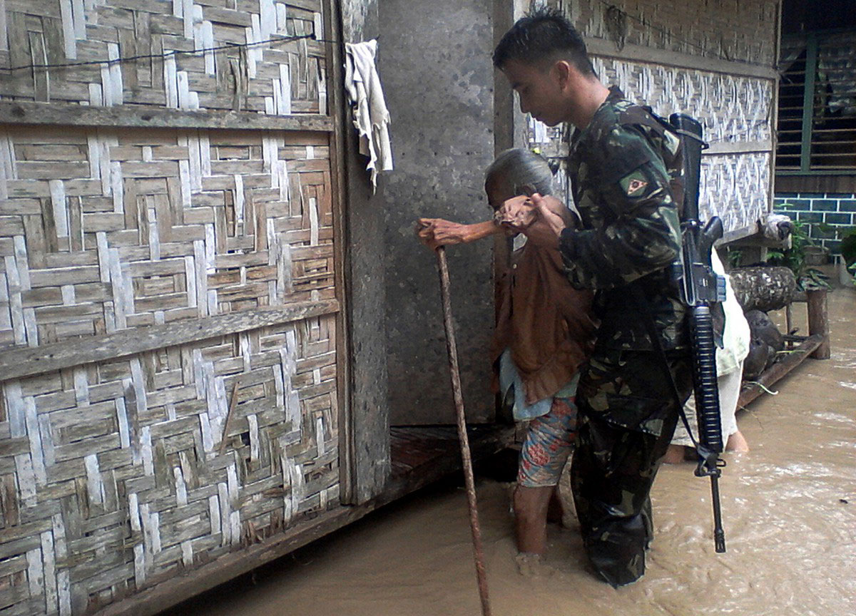 Солдат помогает пожилой женщине на Филиппинах