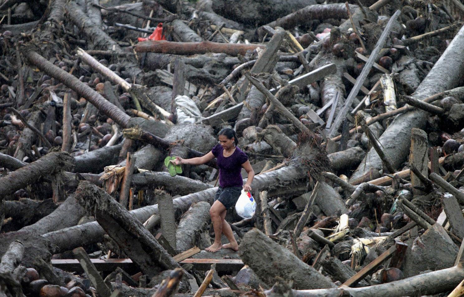 Женщина перебирается через горы мусора, фото
