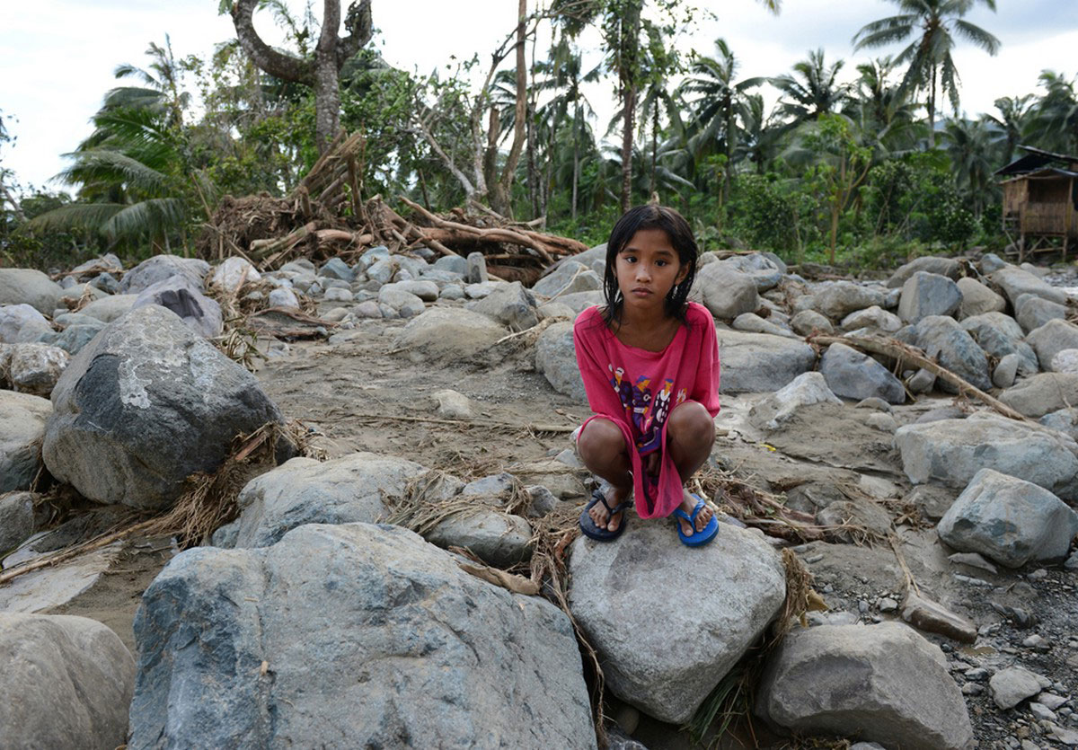ребенок на камнях посте тайфуна Бофа