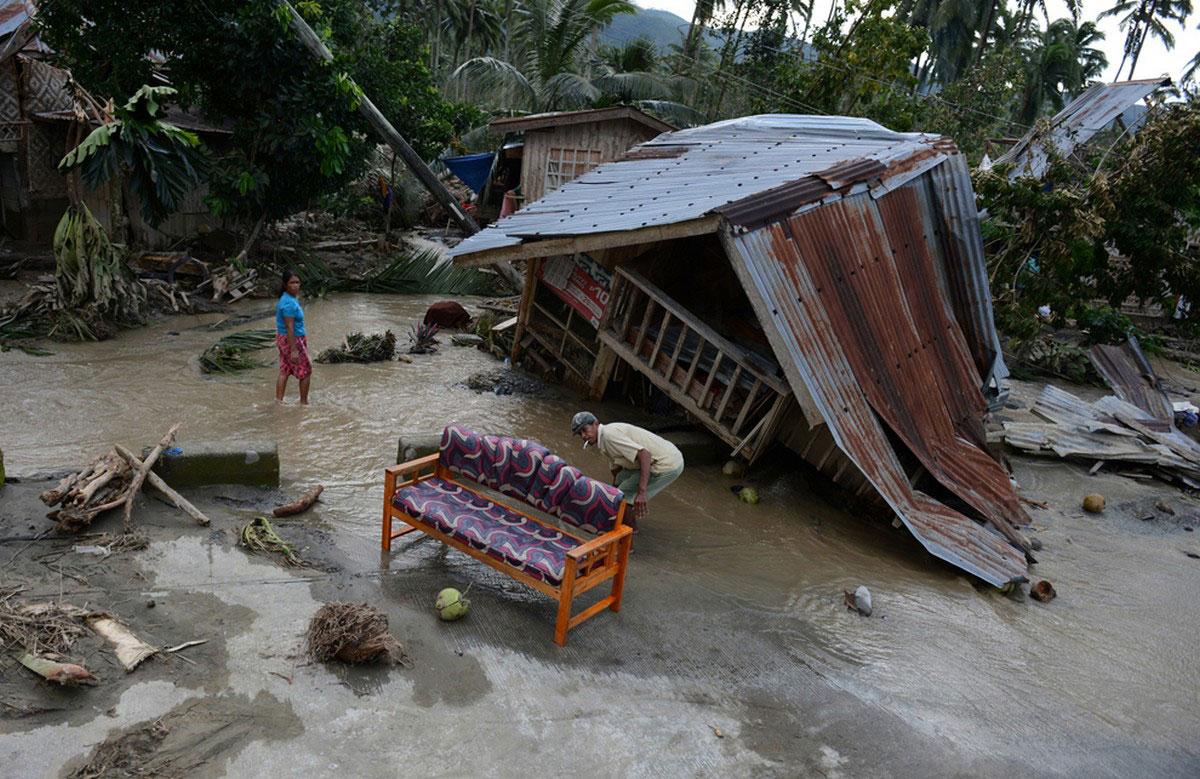 Жители вытаскивают уцелевшую мебель из разрушенных ураганом домов