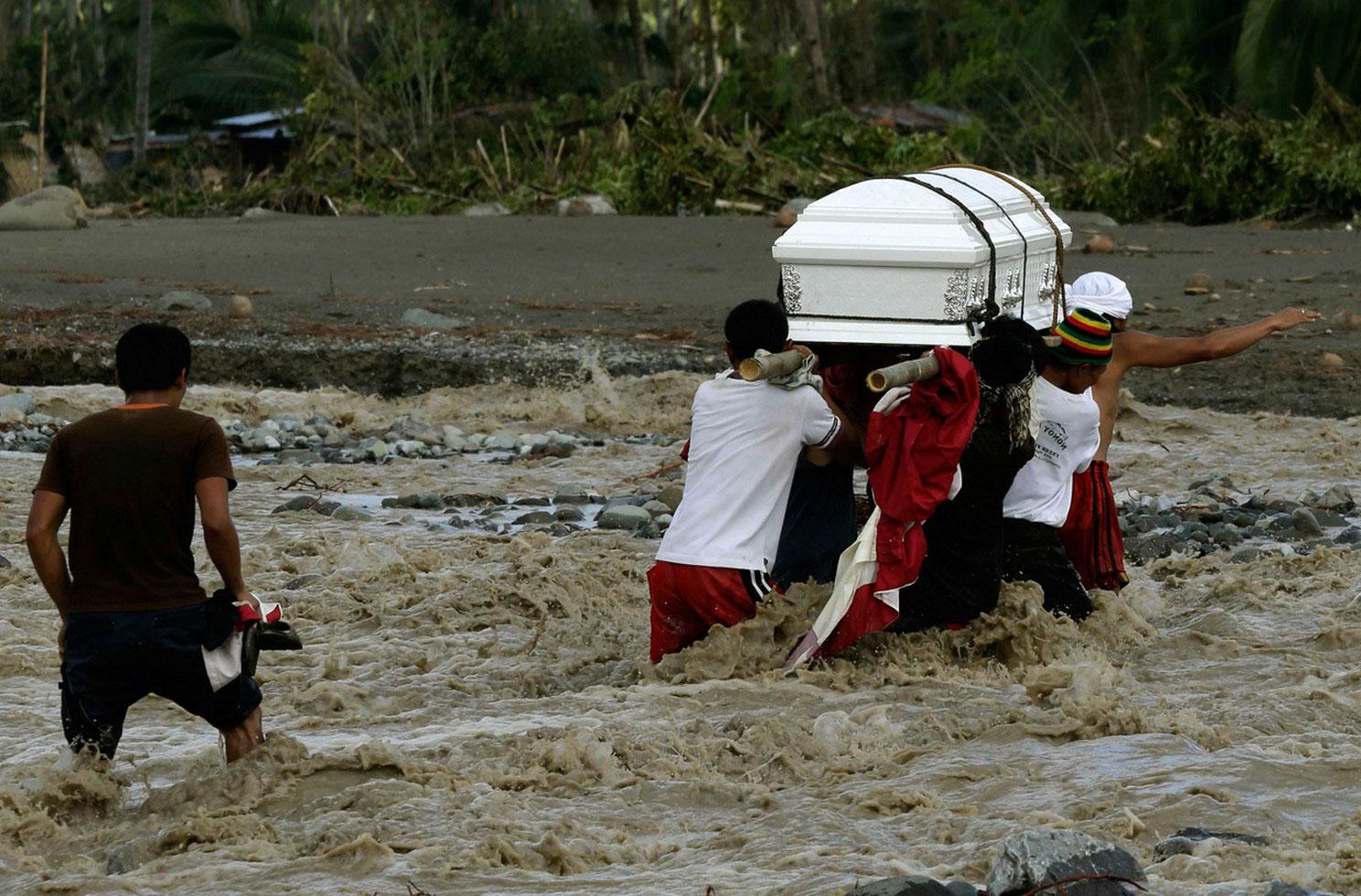 люди несут гробы с жертвами наводнения