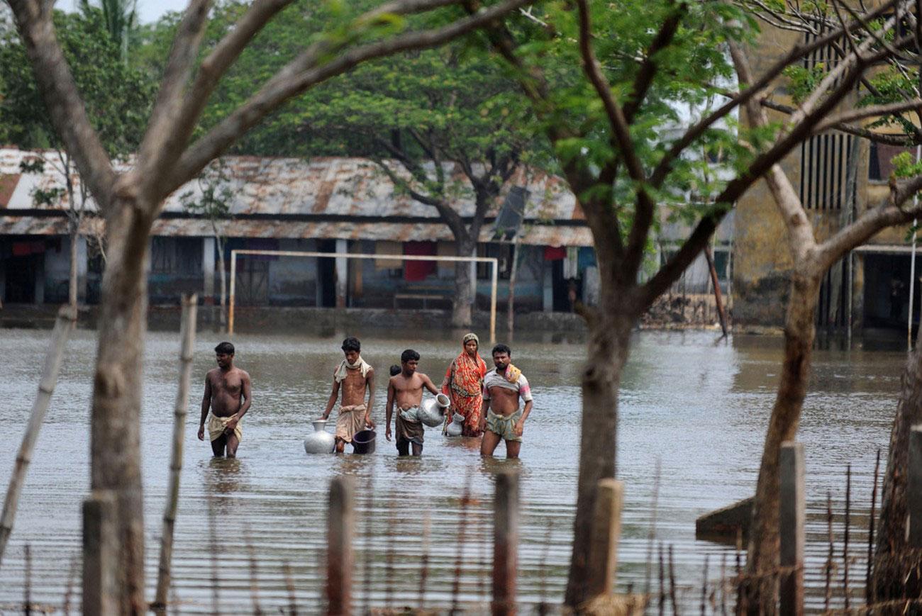 жители передвигаются по затопленным улицам после циклона в Индии