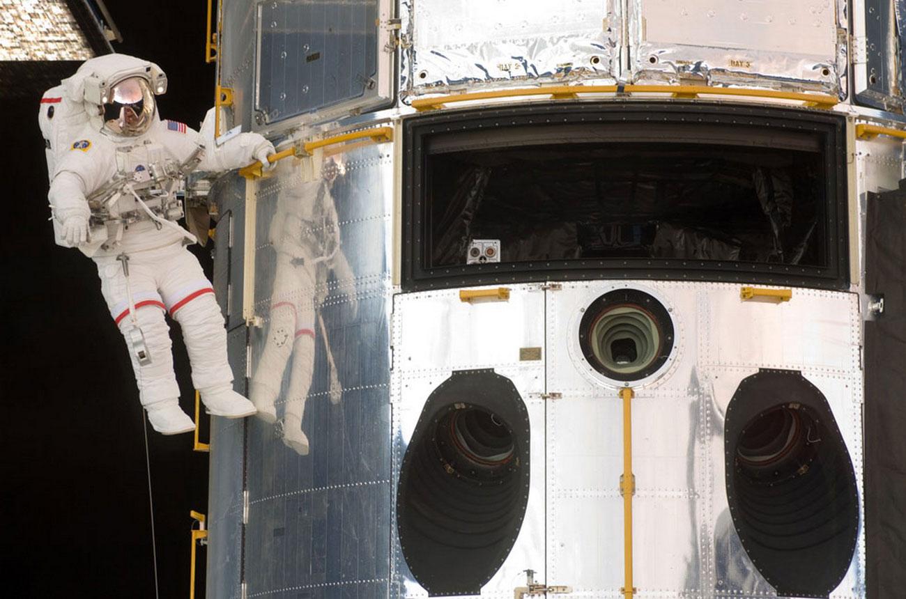 астронавт ремонтирует Хаблл